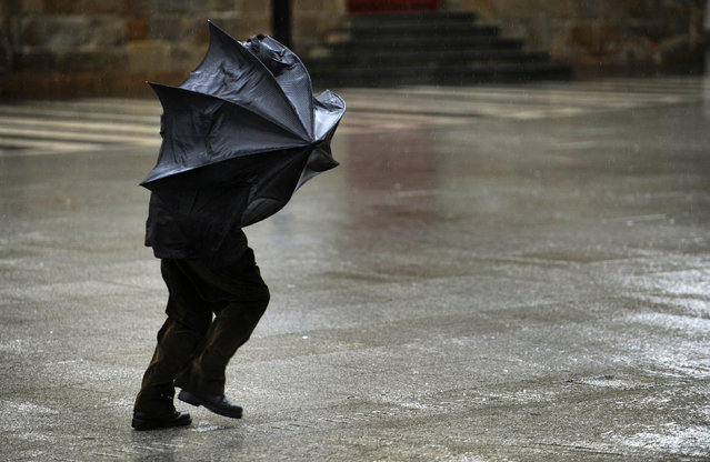 A man tries to hold his umbrella in the midst of strong gusts of wind in Gijon, northern Spain, January 30, 2015. (Photo by Eloy Alonso/Reuters)