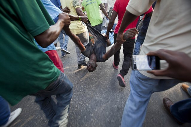 Anti-government protesters carry the body of a demonstrator who was shot to death during clashes with the National Police in Port-au-Prince, Haiti, Saturday, December 13, 2014. Haiti's capital has endured a growing number of violent demonstrations in which protesters are demanding long-delayed elections and the resignations of Prime Minister Laurent Lamothe as well as President Michel Martelly. The protests also spread to other towns, including Gonaives and Cap-Haitien. (Photo by Dieu Nalio Chery/AP Photo)