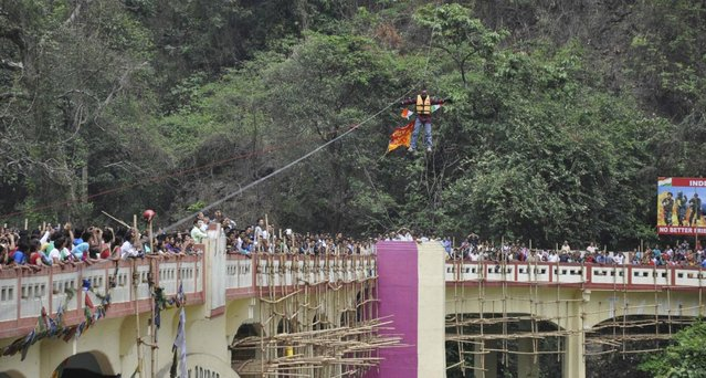 In this Sunday, April 28, 2013 photograph, people watch as Indian Sailendra Nath Roy attempts to cross Teesta river suspended from a zip wire attached to his ponytail moments before his death in Siliguri, West Bengal state, India. Roy who was named a Guinness World Record holder in 2011 for travelling the farthest distance on a zip wire using hair died during the stunt Sunday when he suffered a heart attack. (AP Photo)