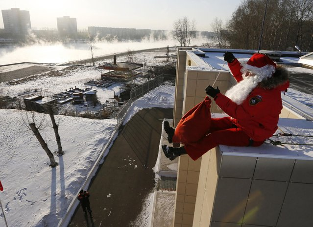 """Alexei Trifonov, a member of the """"Rescuer"""" state regional service dresses as Santa Claus as he prepares to congratulate employees of the Russian Emergencies Ministry and their children ahead of New Year and Christmas in Krasnoyarsk, Siberia December 24, 2014. (Photo by Ilya Naymushin/Reuters)"""