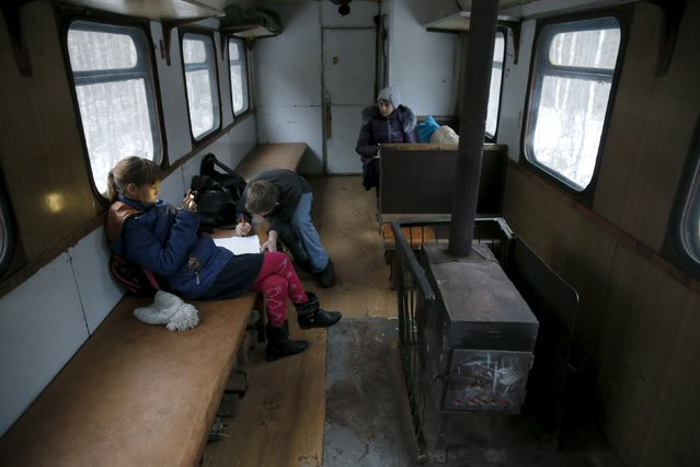 Schoolchildren from the village of Muratkovo study inside a train on the way to school in Sverdlovsk region, Russia, October 16, 2015. Muratkovo does not have a school and so the children have to travel to a neighbouring village to study. The journey takes about 40 minutes. (Photo by Maxim Zmeyev/Reuters)