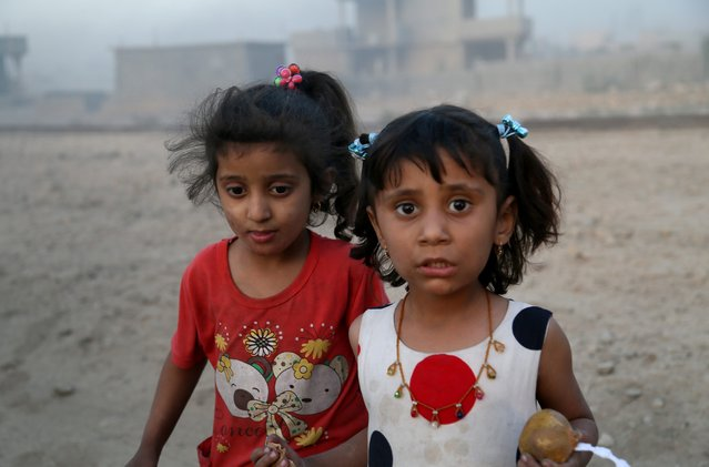 Iraqi internally displaced kids are seen as they have arrived at Al Qayyarah town, secured by Iraqi Army, in Mosul, on October 19, 2016 after they have fled from Daesh controlled areas of Mosul to find safer locations as the operation to retake Iraq's Mosul from Daesh continues. (Photo by Yunus Keles/Anadolu Agency/Getty Images)