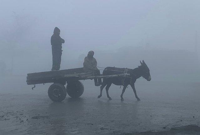 Afghan men ride a donkey cart during a heavy fog in Kabul, Afghanistan, Thursday, November 26, 2020. (Photo by Rahmat Gul/AP Photo)