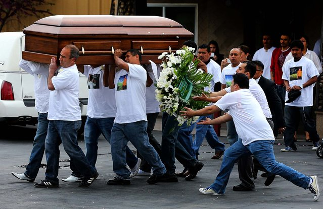 Pallbearers carry the casket of Ricardo Portillo as two people catch flowers that fell off the casket as it is carried to a local church for his funeral in Salt Lake City, on May 8, 2013. Portillo, a soccer official, was punched by a teenage player after issuing a yellow card during a game last week. He died of his injuries this past weekend. (Photo by George Frey/Getty Images)