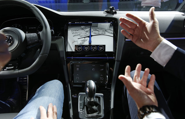 A Volkswagen employee shows off the touch screen in the Golf R Touch during a Volkswagen news conference at the International CES on Monday, January 5, 2015, in Las Vegas. (Photo by John Locher/AP Photo)