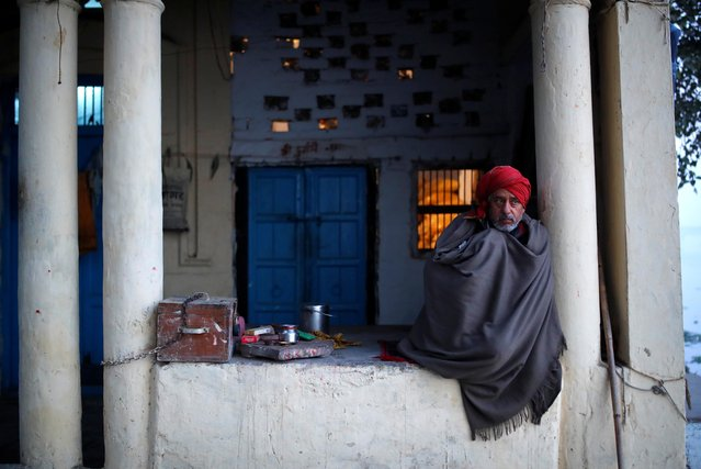 A man wrapped in a quilt sits on the banks of the Yamuna river on a winter morning in New Delhi, India, December 29, 2020. (Photo by Adnan Abidi/Reuters)