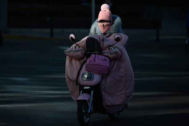 A woman wrapped up for the cold rides a motorcycle along a street on a winter day in Beijing on January 8, 2021 (Photo by Wang Zhao/AFP Photo)