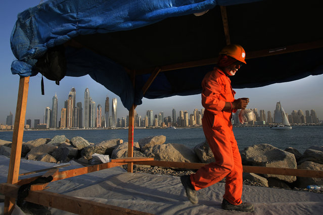 In this September 22, 2015 photo, a laborer carries his lunchbox as he leaves a construction site for the day at the Palm Jumeirah opposite the Marina district, in Dubai, United Arab Emirates. Armies of low-paid migrant workers, many of them from the Indian Subcontinent, leave behind families and travel to Dubai to build soaring towers like those in the Marina. While the wages they come for offer hope of a better life, they are far too meager for most to ever dream of calling the Marina they built home. (Photo by Kamran Jebreili/AP Photo)