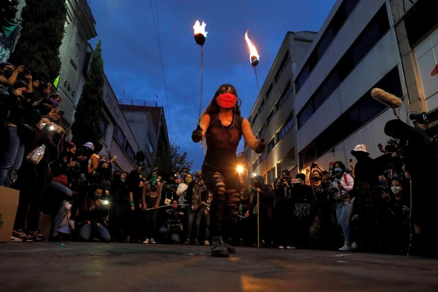 """A woman performs with fire as feminist and crime victims who have been occupying the offices of the governmental Human Rights Commission celebrate an """"anti-grito"""", a day ahead of the traditional """"Grito de Dolores"""", Mexico's annual shout of independence, in Mexico City, Monday, September 14, 2020. The activists, who are demanding justice for victims of femicide, sexual assault, forced disappearances, and other violent crimes, say they will turn the offices into a refuge for victims. (Photo by Rebecca Blackwell/AP Photo)"""