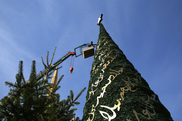 A worker decorates a Christmas tree designed by Lebanese designer Elie Saab in front of the Al-Amin mosque in Beirut, Lebanon, December 9, 2015. Picture taken December 9, 2015. (Photo by Jamal Saidi/Reuters)