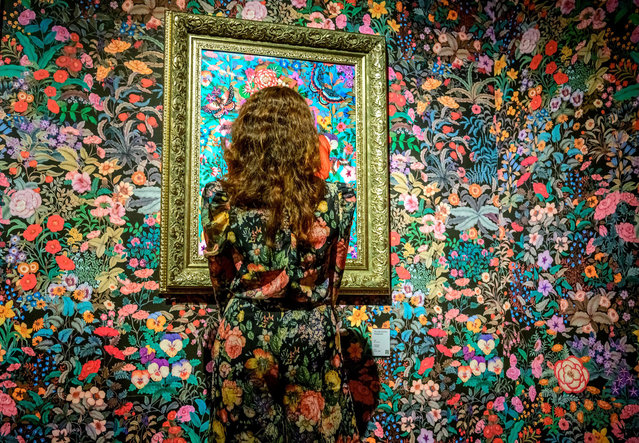 """This photograph taken on January 29, 2021 shows a visitor looking at a painting by artist Phannapast """"Yoon"""" Taychamaythakool exhibited as part of the art project """"Venus in the Shell"""" at the River City Arts and Antiques shopping centre in Bangkok. (Photo by Mladen Antonov/AFP Photo)"""