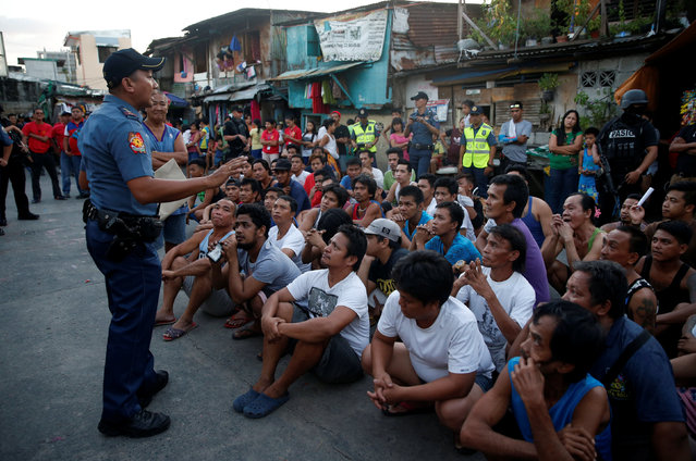 A police officer talks to male residents who are rounded up during an anti-drugs operation in Pasig, Metro Manila in the Philippines, November 9, 2016. (Photo by Erik De Castro/Reuters)