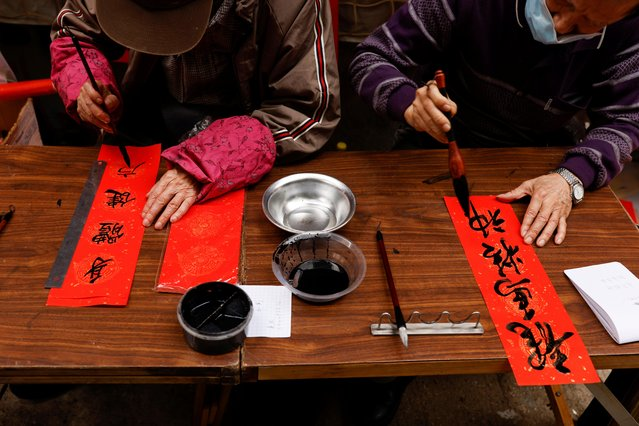 Vendors write Chinese calligraphy with words of blessing on red papers for sale, ahead of the Lunar New Year in Hong Kong, China on February 11, 2021. (Photo by Tyrone Siu/Reuters)