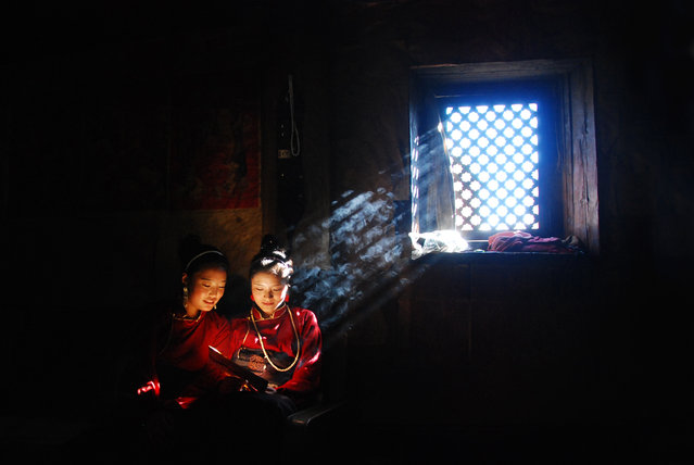 """Shaft Of Light"". This photograph was taken in the house of the two ladies in a rural village. Daylight streamed through the window to provide light in the house. When natural light is unavailable, wood fire is lit to provide light and warmth. Location: Shangri-la, Yunnan, China. (Photo and caption by G Huin/National Geographic Traveler Photo Contest)"