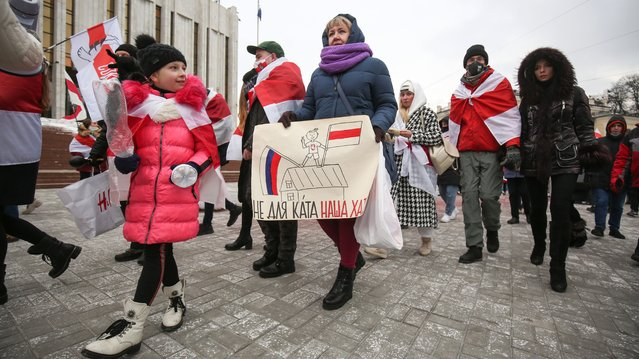 People march with the red and white colors of Belarus's pro-democracy protesters in a show of solidarity in Kyiv on February 7, 2021. (Photo by Serhii Nuzhnenko/Radio Free Europe/Radio Liberty)