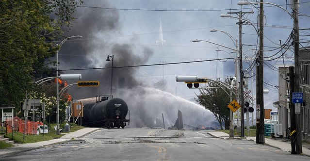 A burning train wagon is seen after an explosion at Lac Megantic, Quebec, July 6, 2013. Several people were missing after four tank cars of petroleum products exploded in the middle of a small town in the Canadian province of Quebec early on Saturday in a fiery blast that destroyed dozens of buildings. (Photo by Mathieu Belanger/Reuters)