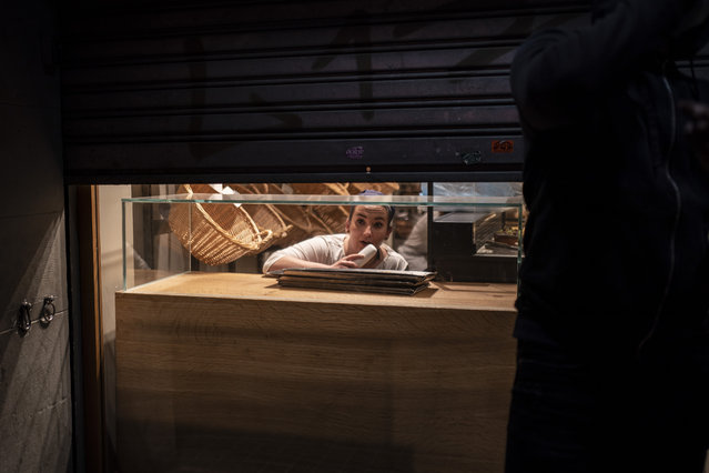 A woman looks from inside a partially closed bakery as demonstrators march outside during a protest condemning the arrest of rap singer Pablo Hasél in Barcelona, Spain, Saturday, February 20, 2021. (Photo by Felipe Dana/AP Photo)