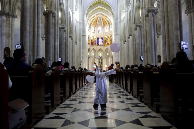 A girl dressed as an angel plays with a balloon as she waits for the start of a distribution of free toys for low-income families and a picture on the lap of one of the Three Wise Men at Almudena Cathedral in Madrid, Spain, December 22, 2015. Traditionally, children in Spain receive their presents delivered by the Three Wise Men on the morning of January 6 during the Christian holiday of the Epiphany. (Photo by Susana Vera/Reuters)