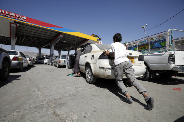 People push a vehicle into a petrol station to refuel amid an acute fuel shortage in Sana'a, Yemen, 31 January 2021. Yemen has been experiencing fuel import shortages due to Saudi-imposed stringent restrictions on fuel imports to war-ridden Yemen over the past few months. (Photo by Yahya Arhab/EPA/EFE)