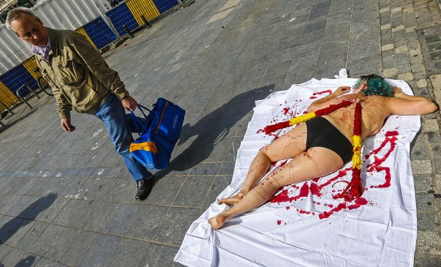 An animal rights protester, covered in fake blood, lies on pavement in central Brussels calling for the abolition of bullfighting, on August 8, 2013. (Photo by Yves Herman/Reuters)