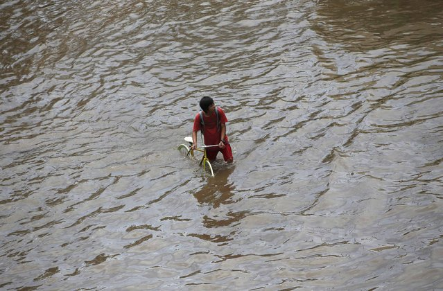 A man walks his bicycle through a flooded street after continuous heavy seasonal rains have flooded many parts of Jakarta February 10, 2015. (Photo by Darren Whiteside/Reuters)