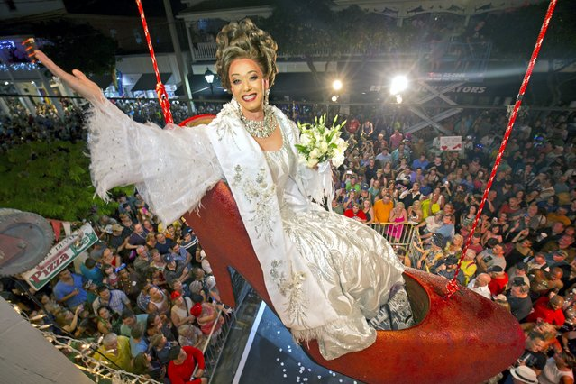 Female impersonator Gary Marion, known as Sushi, hangs in a giant replica of a woman's high heel shoe December 31, 2015, in Key West, Florida. Beginning at about 11:59 p.m. Thursday, the shoe with Sushi in it is to be lowered to Duval Street to mark the beginning of 2016. The Big Red Shoe Drop is one of several of the subtropical island city's takeoffs on New York City's Times Square ball drop. (Photo by Rob O'Neal/Reuters/Florida Keys News Bureau)