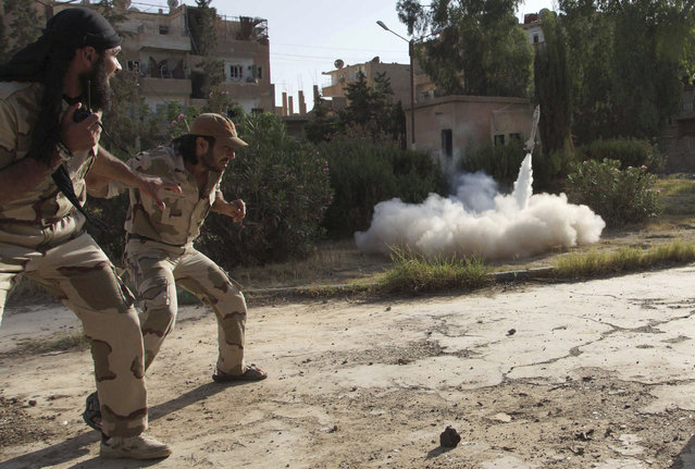 """Members of the """"Free Syrian Army"""" react as they fire a home-made rocket towards forces loyal to the Syrian regime in Deir al-Zor, June 16, 2013. (Photo by Khalil Ashawi/Reuters)"""