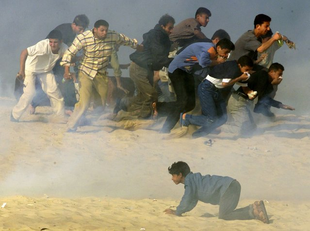 Palestinians try to run away from Israeli soldiers firing teargas during Palestinian-Israeli clashes in the southern Gaza Strip town of Khan Younis in this October 20, 2000 file photo. (Photo by Reinhard Krause/Reuters)