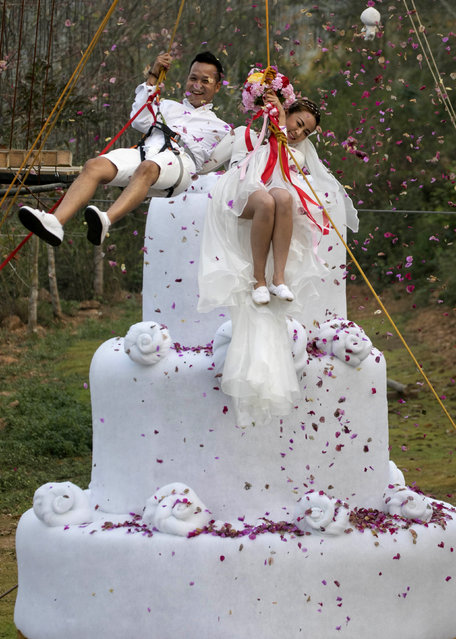 Groom, Chaiyut Phuamgphoeksuk, left and bride, Prontathorn Pronnapatthun right jump from a 3.5 meter high wedding cake, as a part of an adventure-themed wedding ceremony in Ratchaburi Province, Thailand, Friday, February 13, 2015, on the eve of Valentine's Day. (Photo by Wason Wanichakorn/AP Photo)