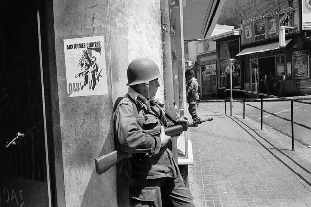 In this May 15, 1962 file photo, a French soldier guards a street corner in Oran, Algeria. French President Emmanuel Macron announced a decision to speed up the declassification of secret documents related to Algeria's seven-year war of independence from 1954 to 1962. On the wall is a poster of the nationalist Secret Armed Organization, calling for citizens to take up arms against Algerian independence. (Photo by Horst Faas/AP Photo/File)
