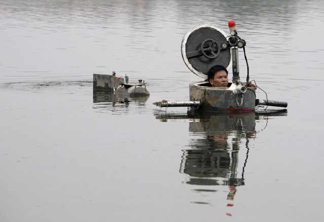 Amateur inventor Tao Xiangli operates his homemade submarine in a lake on the outskirts of Beijing September 3, 2009.  Tao, 34,  made a fully functional submarine, which has a periscope, depth control tanks, electric motors, manometer, and two propellers, from old oil barrels and tools which he bought at a second-hand market. He took 2 years to invent and test the submarine which costs 30,000 yuan ($4,385). (Photo by Christina Hu/Reuters)
