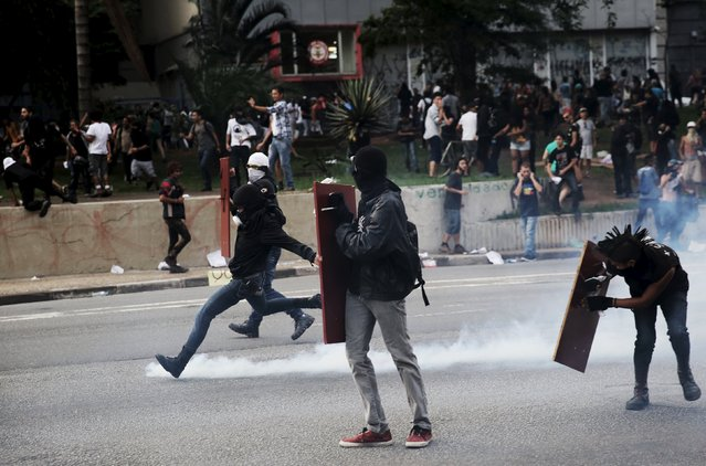 A demonstrator (L) protester kicks a teargas canister fired by riot police during a protest against fare hikes for city buses in Sao Paulo, Brazil, January 8, 2016. (Photo by Nacho Doce/Reuters)