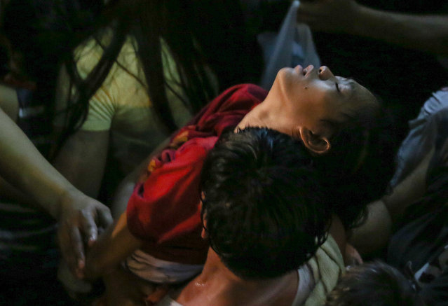 A Filipino devotee is carried away after getting unconscious during a procession as the image of Black Nazarene enters a church to end a 20 hours procession in Manila, Philippines, Sunday, January 10, 2016. Two people died as more than a million barefoot devotees joined the Philippines' largest religious procession, honouring a centuries-old statue of Jesus Christ on Saturday, officials said. (Photo by Mark R. Cristino/EPA)