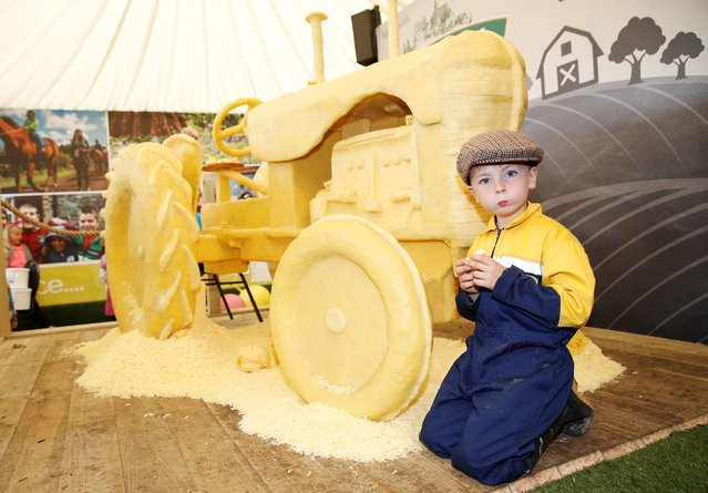 Sitting beside the cheese tractor was Bill Cahill 5 from Ballingarry, Tipperary to celebrate the upcoming launch of Lidl's new range of Rathdarragh Irish cheese, world famous food artist Prudence Staite hand sculpted a 1950's style Massey Harris tractor out of Irish cheddar cheese at this week's National Ploughing Championships. (Photo by Sasko Lazarov/Photocall Ireland)