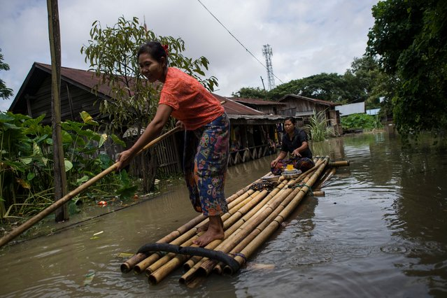 A woman steers a bamboo-raft along a flooded road in Taungnu township of Bago region in Myanmar on August 31, 2018. (Photo by Ye Aung Thu/AFP Photo)