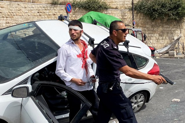 An Israeli police officer holds his weapon as he stands in front of an injured Israeli driver moments after witnesses said his car crashed into a Palestinian on a pavement during stone-throwing clashes near Lion's Gate just outside Jerusalem's Old City on May 10, 2021. (Photo by Ilan Rosenberg/Reuters)