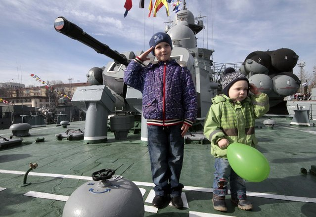 Children salute onboard a Russian warship during celebrations for the Defender of the Fatherland Day in Sevastopol, Crimea February 23, 2015. (Photo by Pavel Rebrov/Reuters)