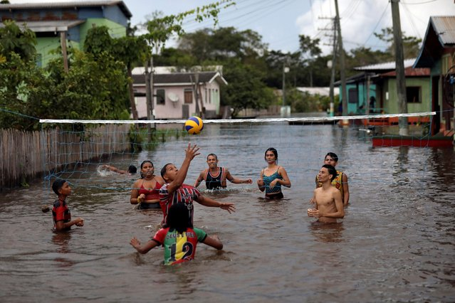 Residents play volleyball in a street flooded by the rising Solimoes river, one of the two main branches of the Amazon River, in Anama, Amazonas state, Brazil on May 14, 2021. (Photo by Bruno Kelly/Reuters)