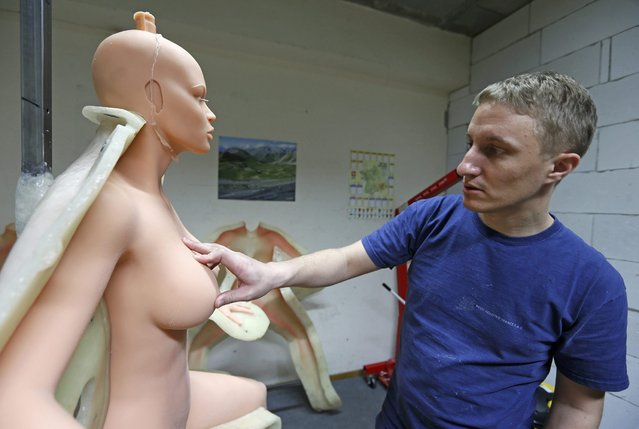 Eric, an employee at the Dreamdoll company, inspects a silicone dream doll as he removes it from a mold at their workshop in Duppigheim near Strasbourg, December 2, 2014. (Photo by Vincent Kessler/Reuters)