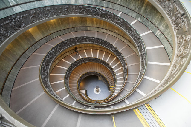A visitor walks down a staircase, designed by architect Giuseppe Momo in 1932, as she leaves the Vatican Museums, at the Vatican, Monday, February 1, 2021. The Vatican Museums reopened Monday to visitors after 88 days of shutdown following COVID-19 containment measures. (Photo by Andrew Medichini/AP Photo)