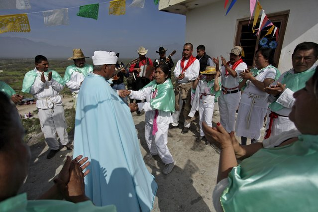 A medium or materia (L) dances with a penitent at the Cerro de la Campana (or hill of the bell) during celebrations for El Nino Fidencio in the town of Espinazo, on the outskirts of Monterrey March 19, 2015. (Photo by Daniel Becerril/Reuters)