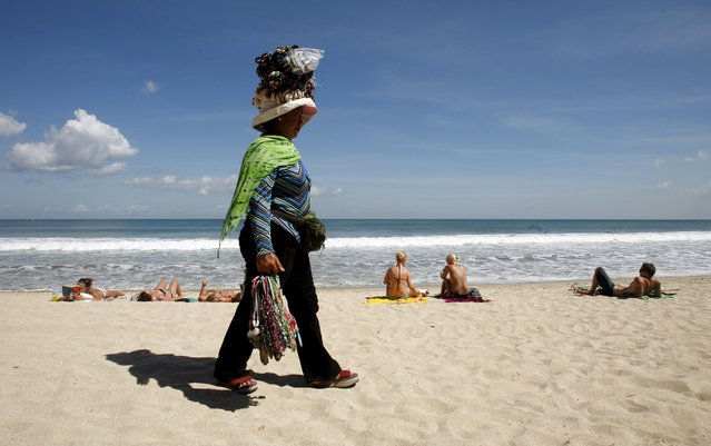 A woman selling souvenirs walks through Kuta beach in Bali June 5, 2008. Indonesia is expected to report tourist arrivals in December this week. (Photo by Murdani Usman/Reuters)