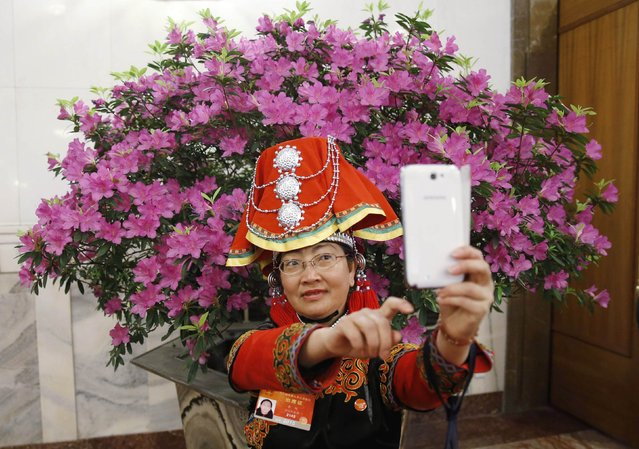 A minority delegate (C) in traditional costume takes a selfie as she arrives before the third plenary meeting of the National People's Congress, China's parliament, at the Great Hall of the People, in Beijing, March 12, 2015. (Photo by Kim Kyung-Hoon/Reuters)
