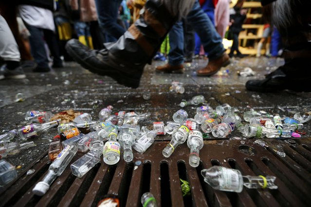 """Revellers walk past an empty bottles of alcohol during the """"Weiberfastnacht"""" (Women's Carnival) celebrations in Cologne, Germany February 4, 2016. (Photo by Wolfgang Rattay/Reuters)"""
