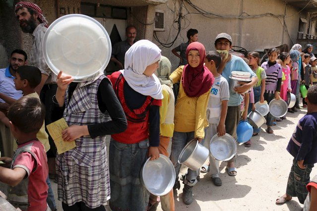 Children carry buckets as they queue to receive free meals from a soup kitchen in the besieged town of Deir al-Asafir in the Eastern Ghouta of Damascus May 19, 2015. (Photo by Amer Almohibany/Reuters)