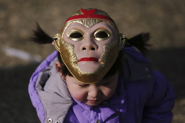 A girl wearing a monkey mask atop her head is seen at the Longtan park as the Chinese Lunar New Year, which welcomes the Year of the Monkey, is celebrated in Beijing, China February 9, 2016. (Photo by Damir Sagolj/Reuters)