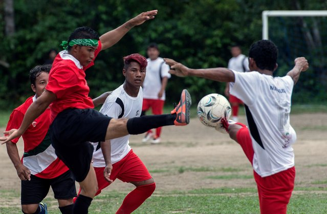 Indigenous football players vie for a ball during the final match of Peladao, the amateur football tournament, in Manaus, Amazonas state, Brazil, on November 24, 2013. (Photo by Yasuyoshi Chiba/AFP Photo)