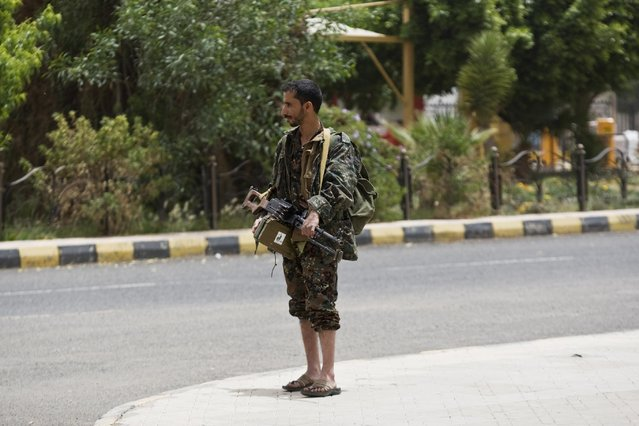"A Shiite rebel, known as Houthi, wearing an army uniform, stands guard in front of the international airport in Sanaa, Yemen, Saturday, March 28, 2015. Yemen's President Abed Raboo Mansour Hadi, speaking at the opening session of an Arab summit in Egypt on Saturday, called Shiite rebels who forced him to flee the country ""stooges of Iran"", directly blaming the Islamic Republic for the chaos there and demanding airstrikes against rebel positions continue until they surrender. (Photo by Hani Mohammed/AP Photo)"