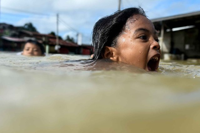 A girl swims in floodwaters in Malaysia' s northeastern town of Rantau Panjang, which borders Thailand, on January 5, 2017 Floods in two northeast Malaysian states have now forced almost 23,000 people from their homes and extra relief centres have been opened, rescue officials said on January 4. (Photo by Mohd Rasfan/AFP Photo)