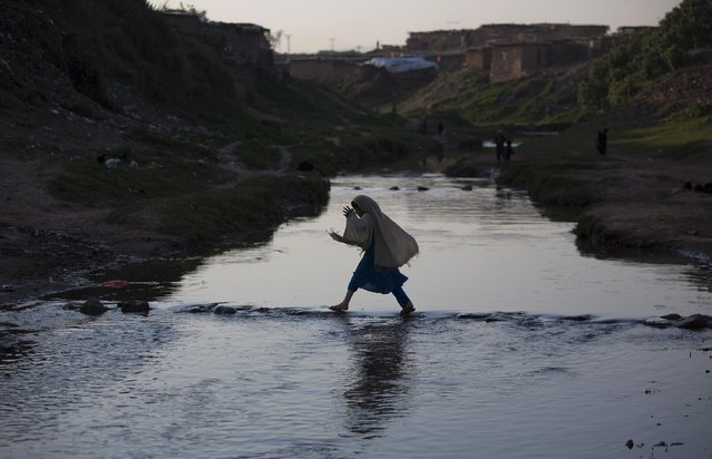 In this Friday, March 20, 2015 file photo, a displaced Pakistani girl, who fled from a Pakistani tribal area where security forces are fighting against militants, crosses a stream in suburbs of Islamabad, Pakistan. (Photo by B. K. Bangash/AP Photo)